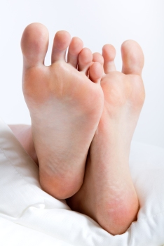 Woman's feet in bed on a Sunday morning